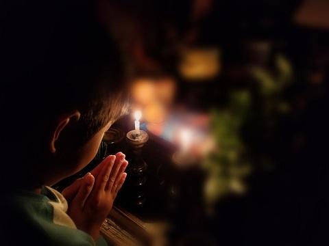 仏壇・仏具の前でお祈りしている子供