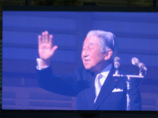 スクリーンに録画されたお出ましの映像天皇陛下の笑顔