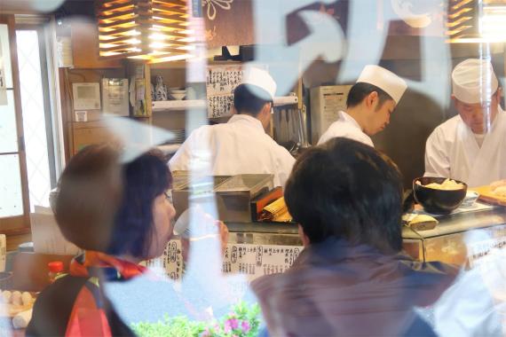 白い割烹着で寿司を握る職人
