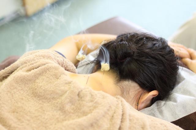 ツボにお灸をする女性