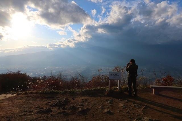 陣馬形山の山頂から写真を撮る登山者