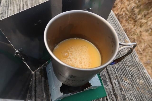 鍋(コッヘル)の中にコーンスープを入れて固形燃料ストーブで温める