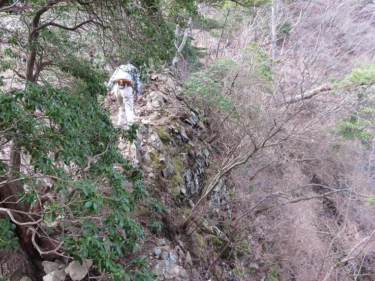 崖沿いに登山ルート歩いてる登山者