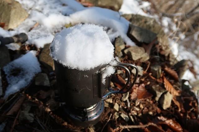 カップを使って雪を解かし水を作る様子