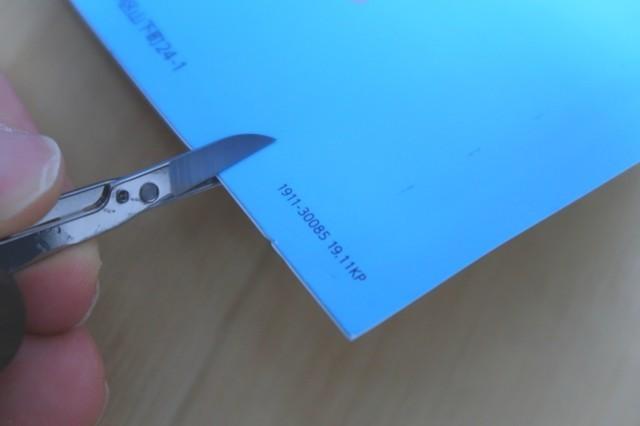 ツールナイフの小さなハサミで封筒を切っている様子