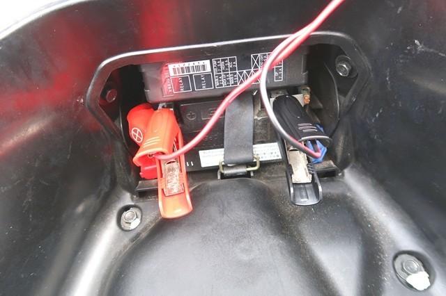 PCXのバッテリーに充電器をセットしている様子