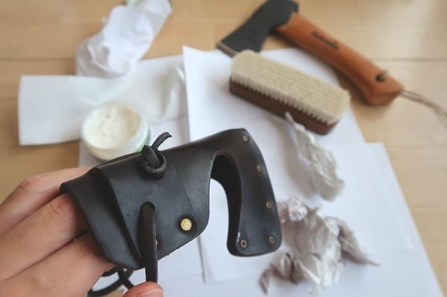 ハルタホース革製の斧カバーを磨いて掃除している様子