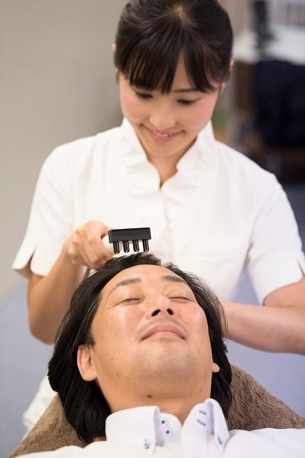 ハゲの原因となる皮脂の分泌を高周波(ビームライザー)を使ってアプローチしている様子