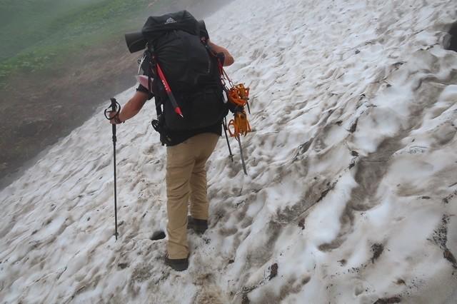 石転び沢雪渓の最大斜度を歩く登山者
