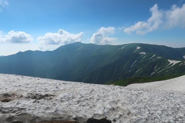 雪渓越しの飯豊山の山頂とダイグラ尾根