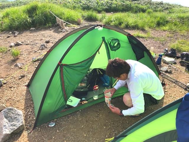 テント場で設営中の登山者