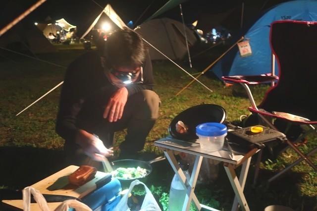 キャンプ料理中のキャンパー