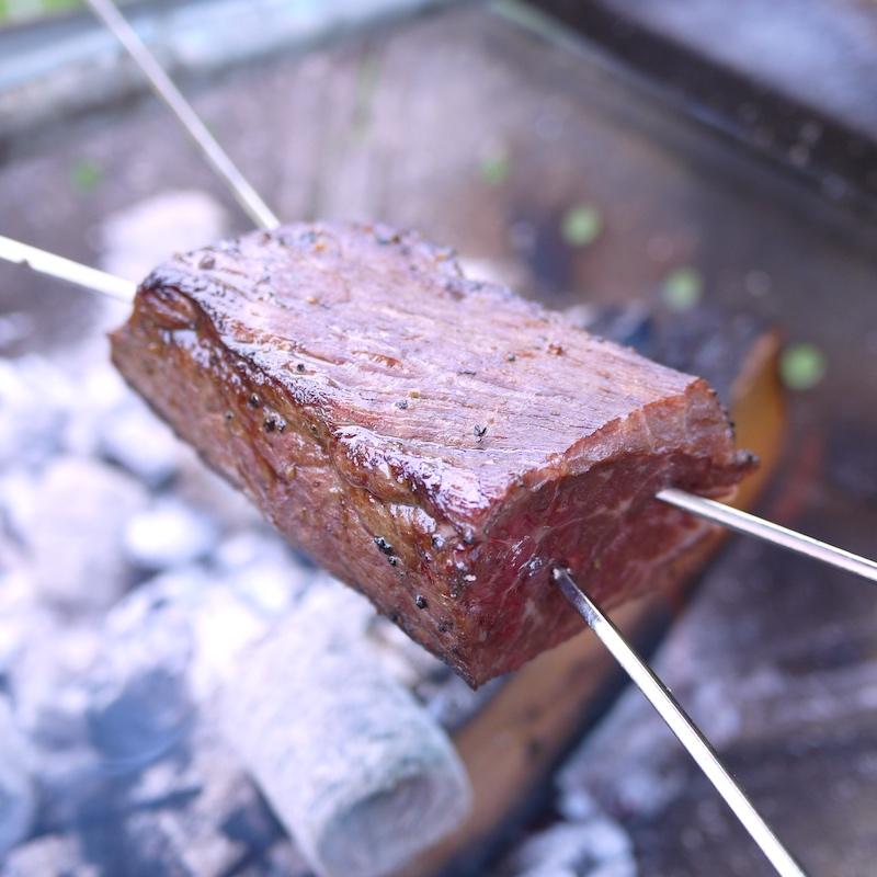 炭火でじっくり牛肉を焼く