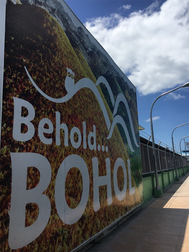 ボホール島の港にある、チョコレートヒルズと眼鏡猿ターシャのイラストが載った看板
