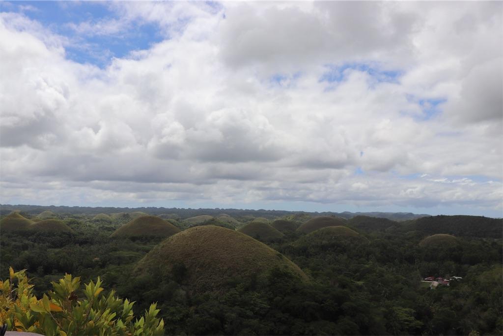 チョコレート色に染まる丘の全体を見渡せる丘と空の写真