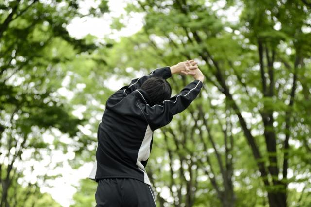 公園でセルフストレッチをする男性