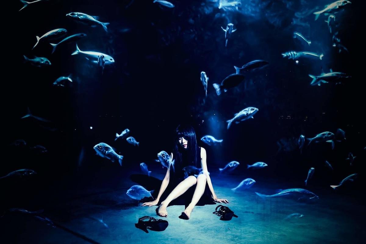 魚が回遊する中で青白くうつむく女性