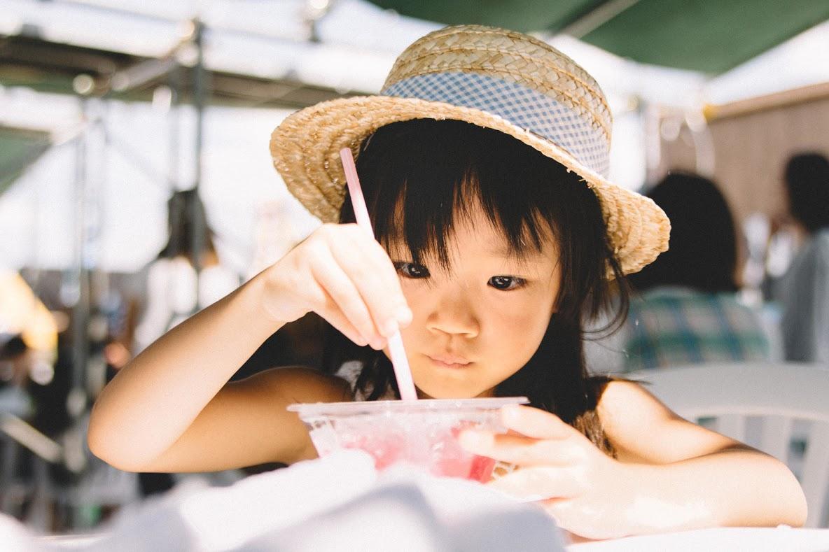 おいしそうにかき氷を食べている麦わら帽子の女の子