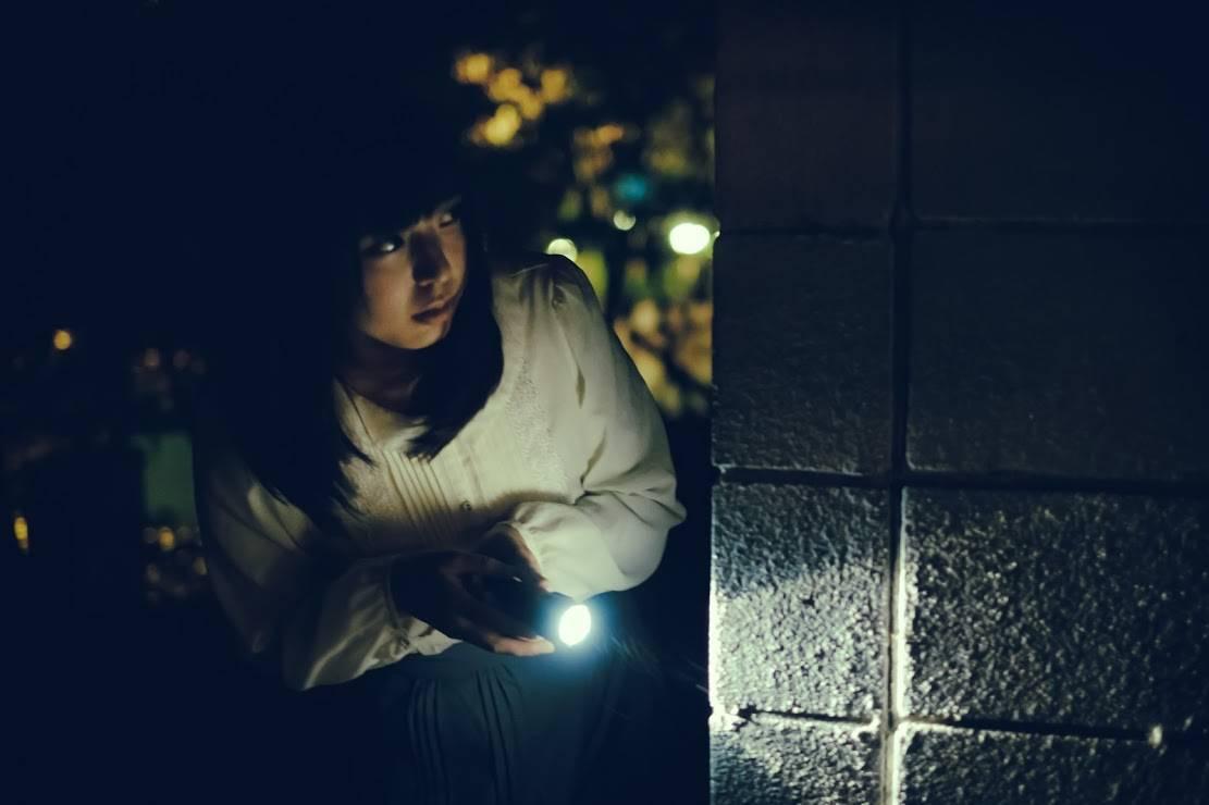 暗がりでライトを照らしながら不安そうに様子を見る女性