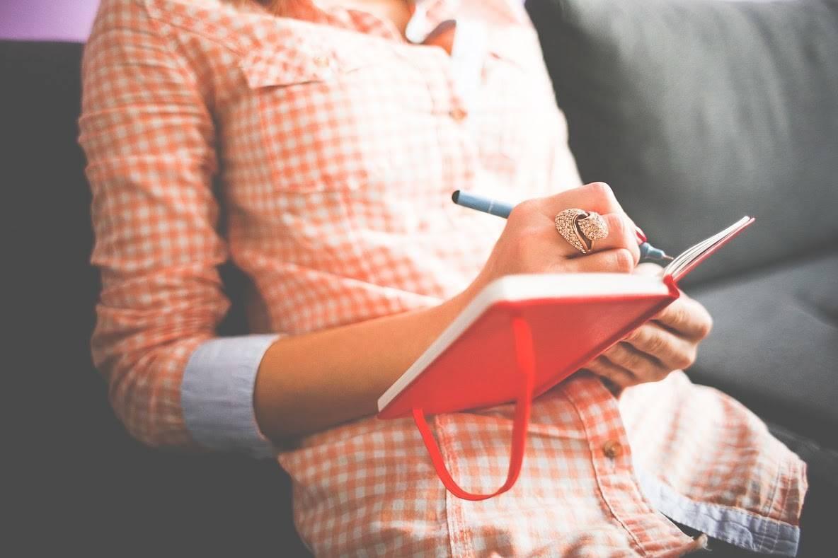 赤い手帳に何かを書いている女性
