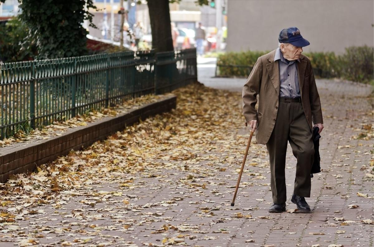 老人が杖をついて歩いている写真