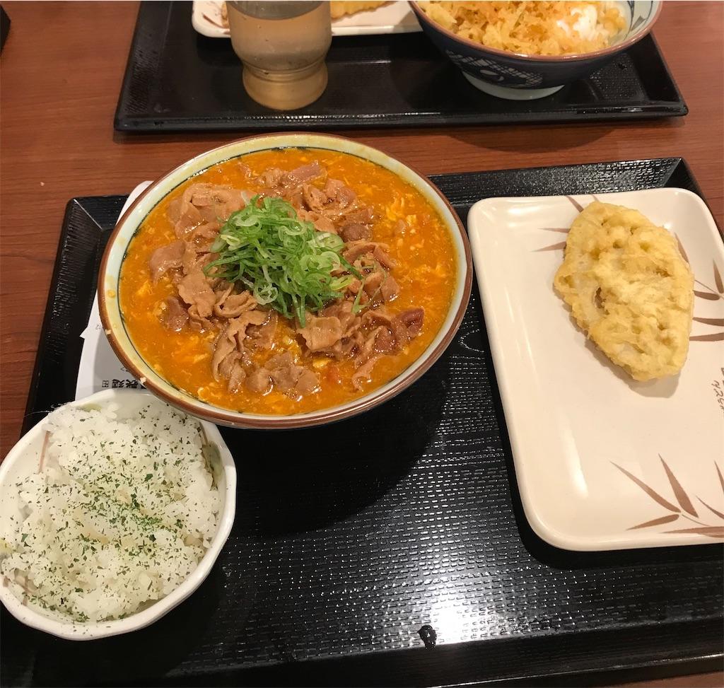 丸亀製麺のトマたまカレーうどん(豚肉入り)の並とれんこんの天ぷら(写真右)。