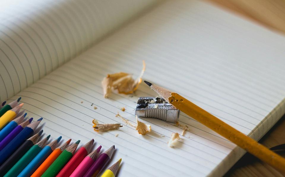 ノートの上の鉛筆と鉛筆削り