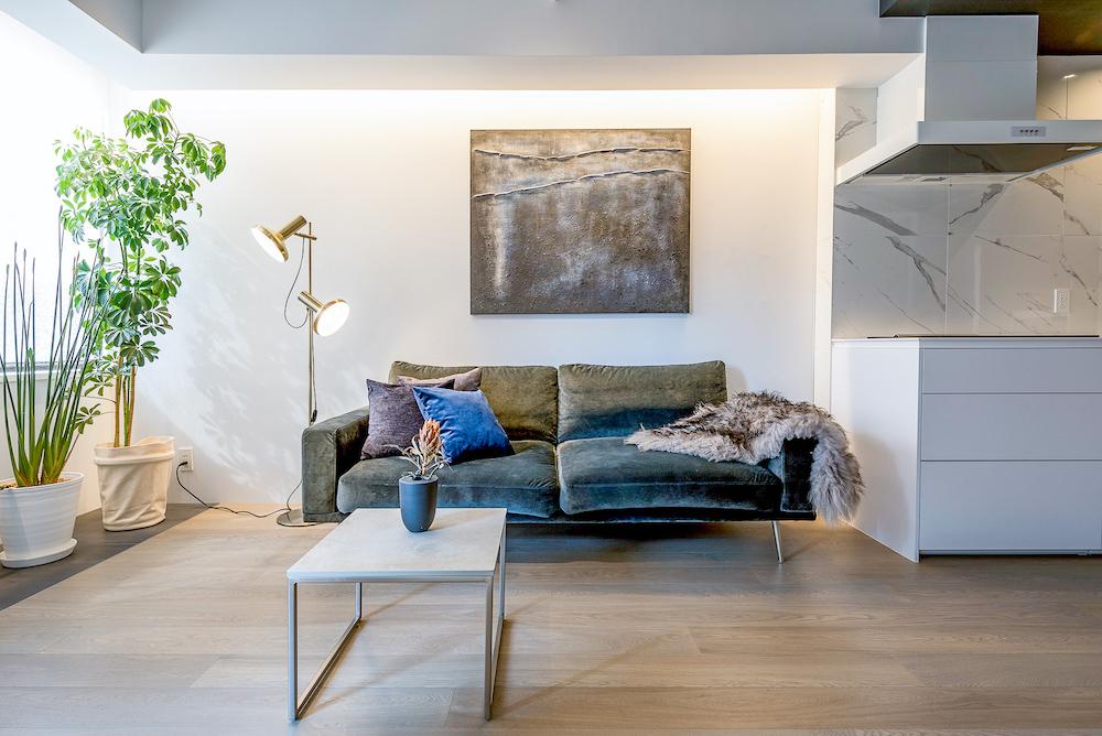 リビングのソファと白いキッチン
