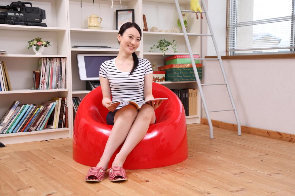 女性と赤い丸いイス部屋