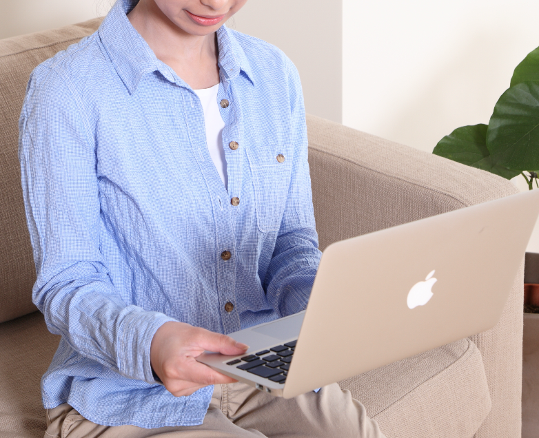 女性ソファでノートパソコン