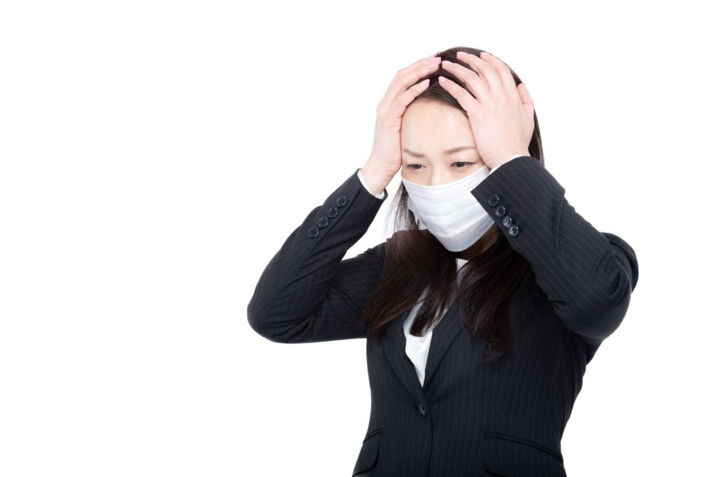 風邪をひいて頭を抱える女性