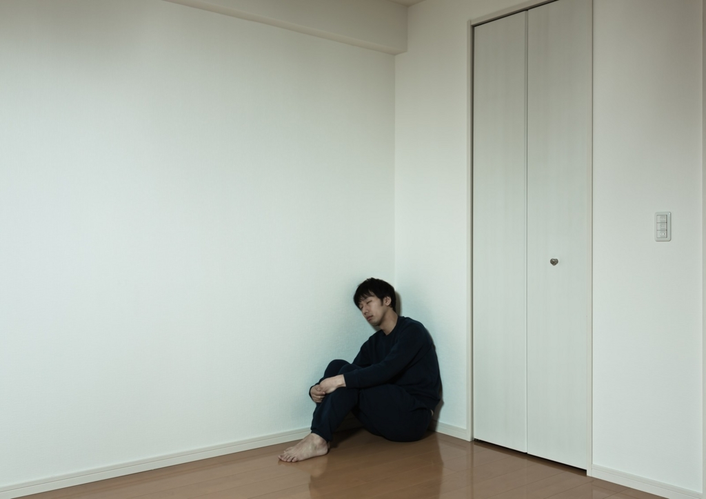 壁にもたれて疲れている男性