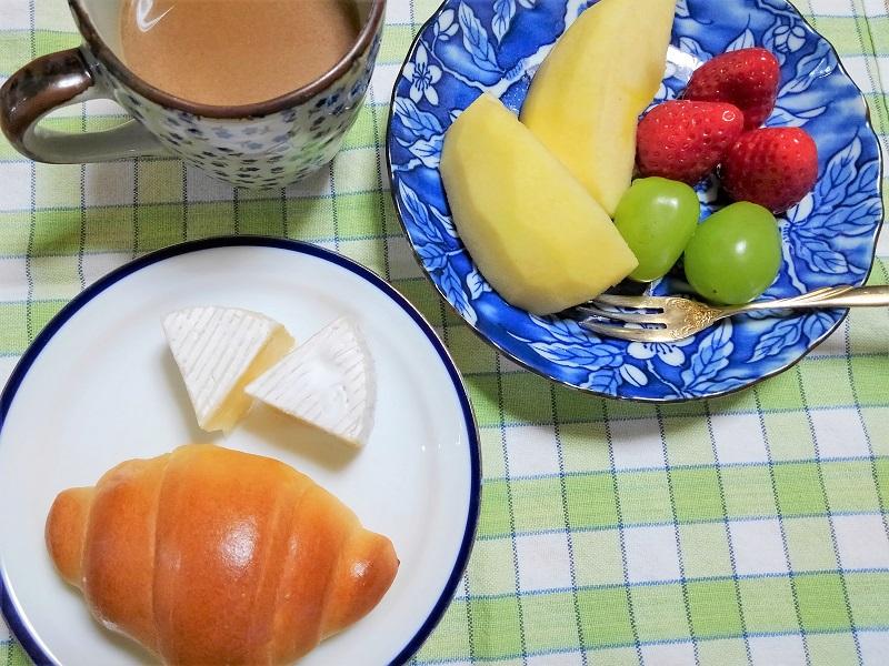 食卓に並べられたパン、カマンベールチーズ、フルーツとコーヒー