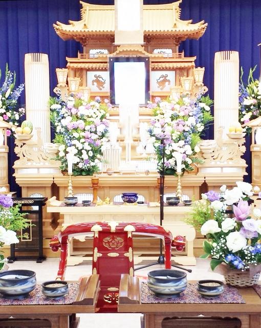 葬儀の白木祭壇と赤い僧侶の曲録椅子