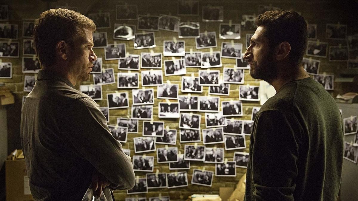 壁に写真を貼るカールとアサド