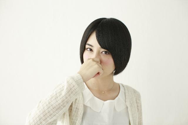 臭いを避けるために鼻をつまむ女性