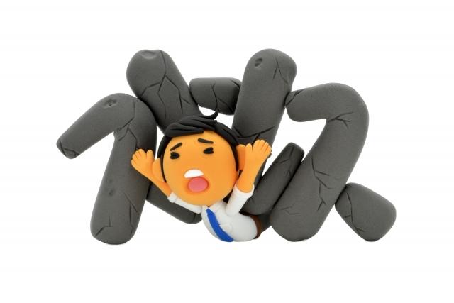 「ストレス」という文字に押しつぶされる男性人形