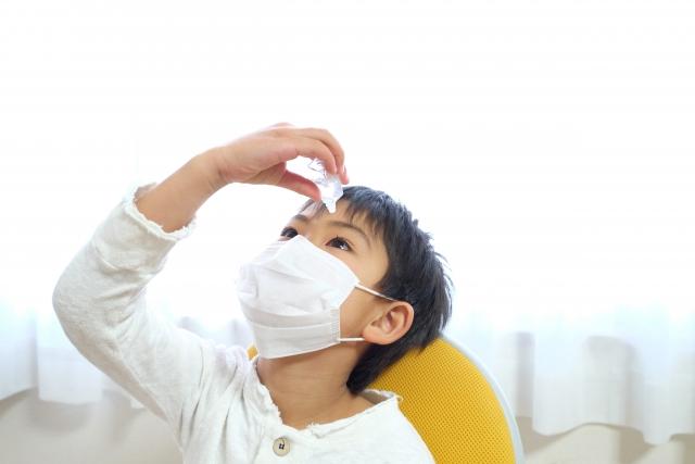 マスクをして目薬をさす男の子