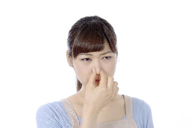 鼻をつまんで顔をしかめる女性