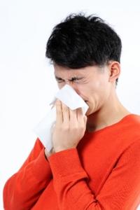 花粉症で鼻を鼻をかむ男性