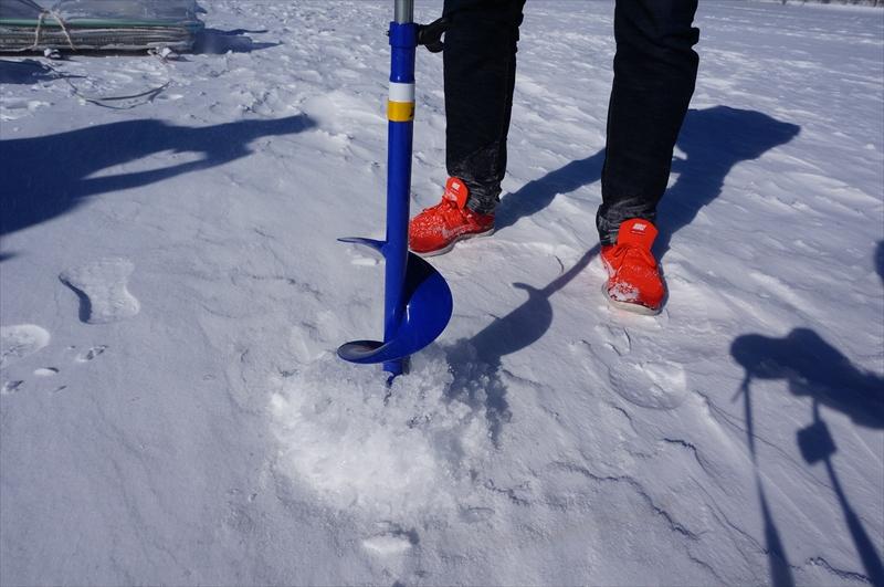 湖の氷にドリルで穴を