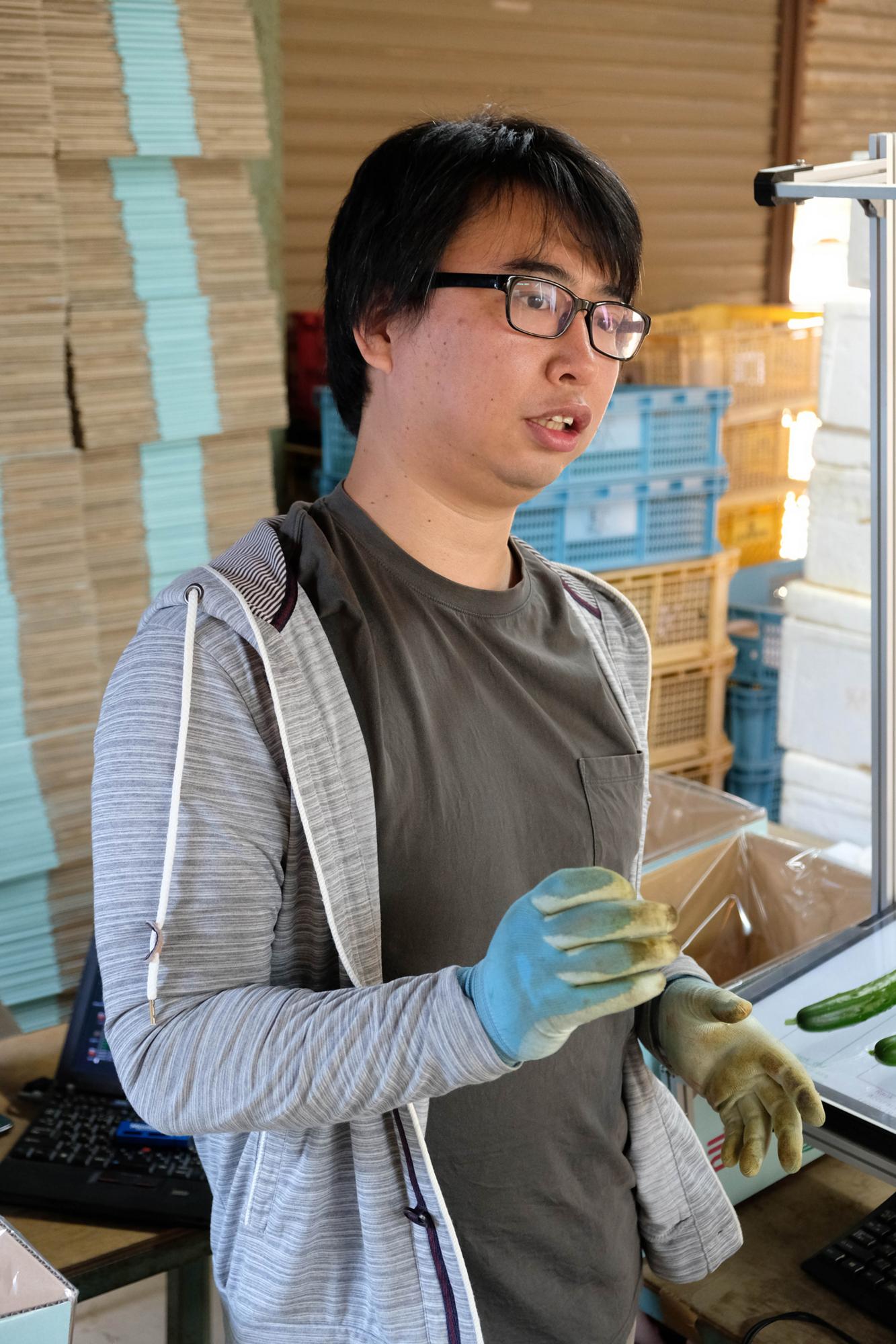きゅうりの仕分けについて説明する小池誠さん。以前は名古屋で組み込み系のエンジニアをしていた