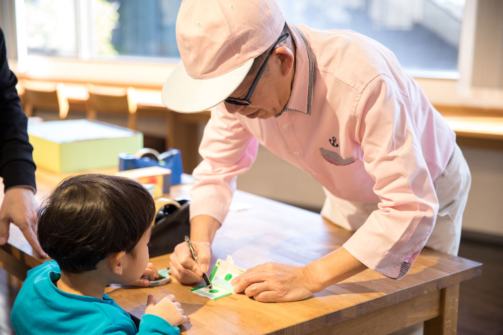 牛乳パックを使った工作を教える久保田さん