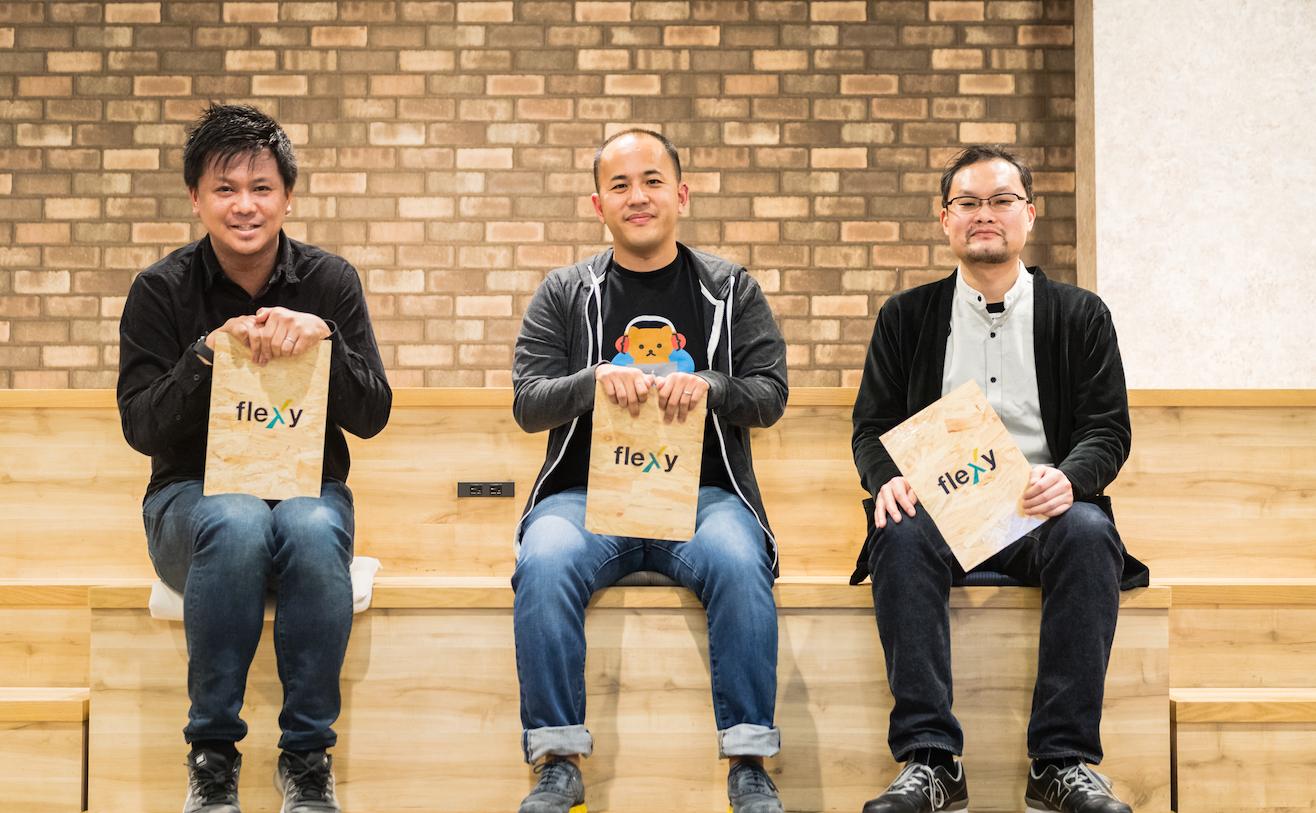 three men with flexy logo bords