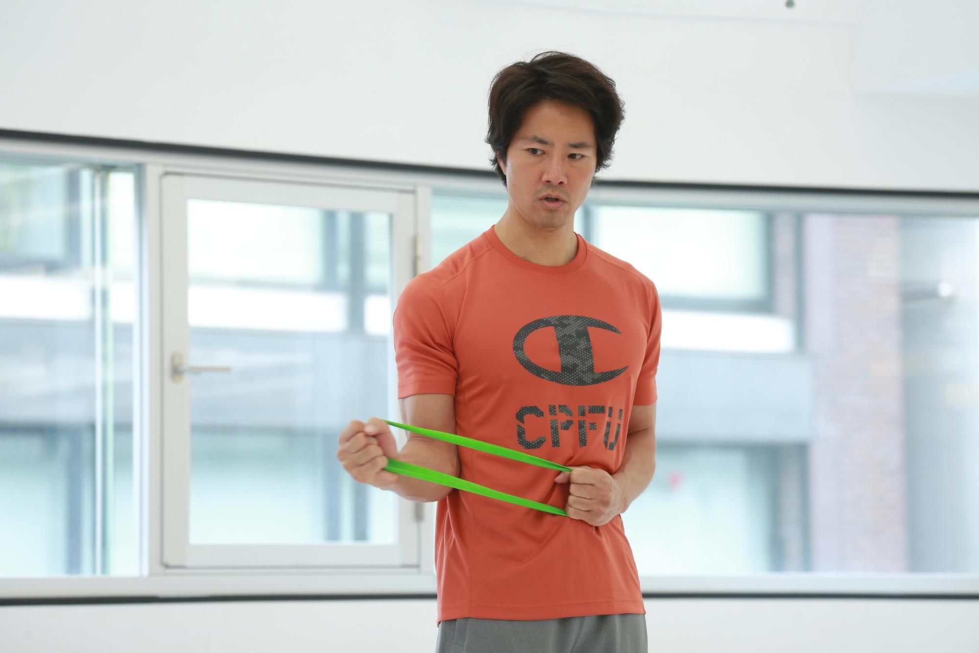 ケイン・コスギのゲームのための筋トレ術。ゴムバンドを引っ張り、肩の筋肉をほぐす