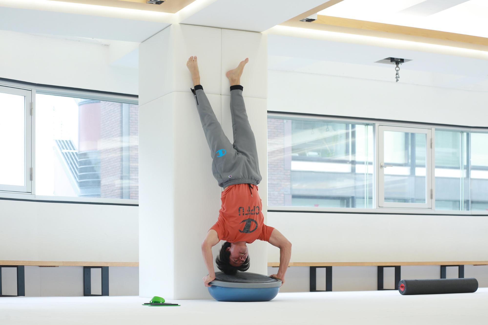 ケイン・コスギのゲームのための筋トレ術。ドーム状のトレーニングツール「BOSU プロバランストレーナー」を使って逆立ち腕立て伏せをすると、より効果的。