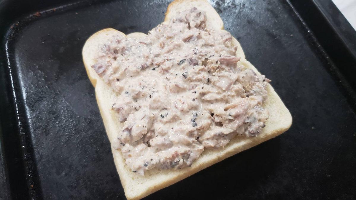 バズレシピ・リュウジさんの簡単レシピ。「鯖トースト」の作り方。容器に汁を切った鯖缶とマヨネーズ、コンソメ、レモン汁を混ぜる(☆)。食パンの上に(☆)を載せて350度のグリルで8分焼けば完成