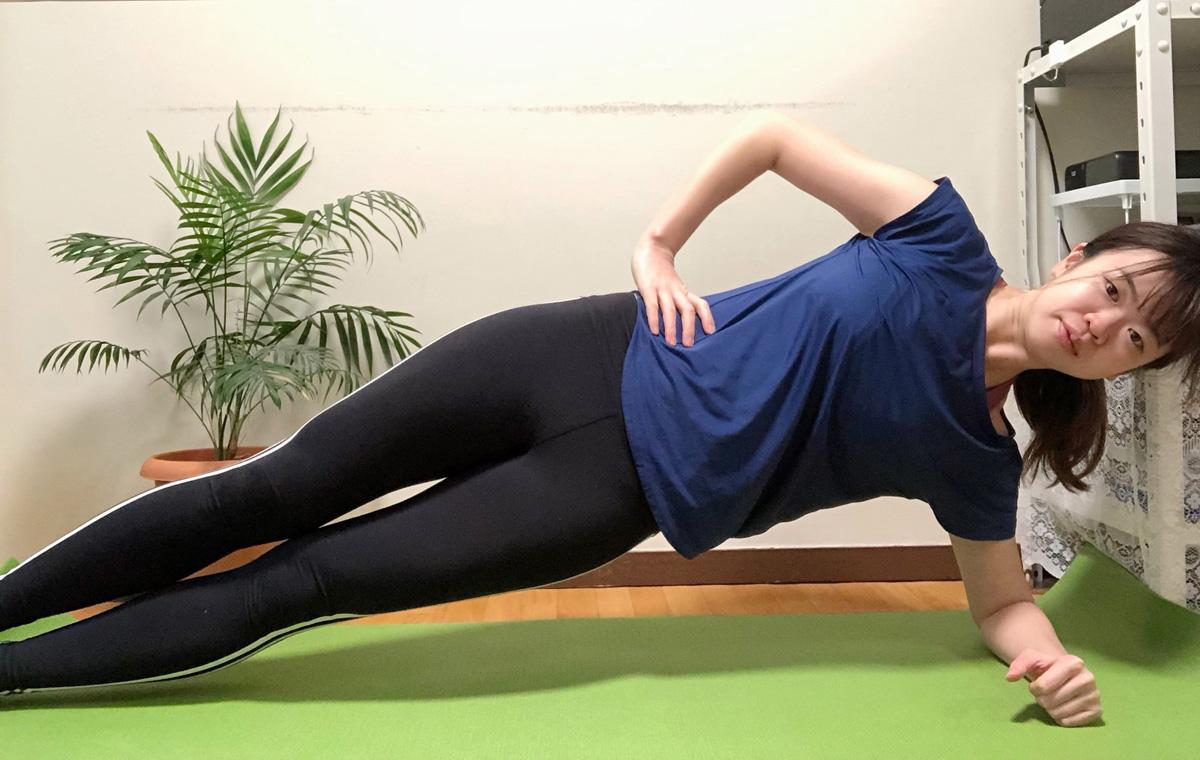 サイドプランク1。横向きになり、床側のひじを肩の下において上体を持ち上げる