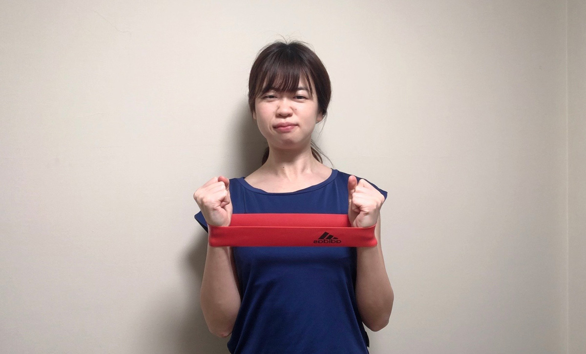 手首に装着したゴムバンドを胸の前でピンと張りながら胸の前にこぶしがくるように肘を曲げる