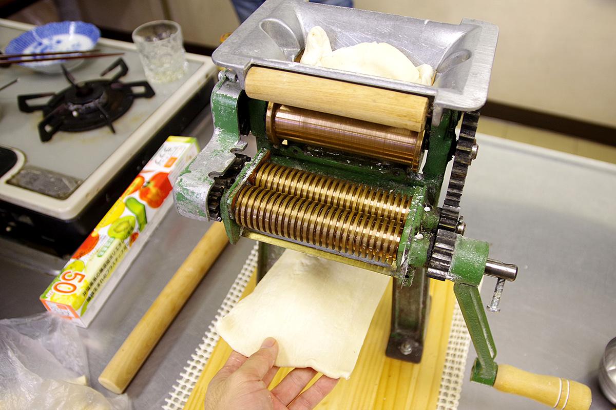生地をまとめて寝かせてから、家庭用製麺機という機械で均一に伸ばしていきます。ここまではうどん作りとほぼ同じ